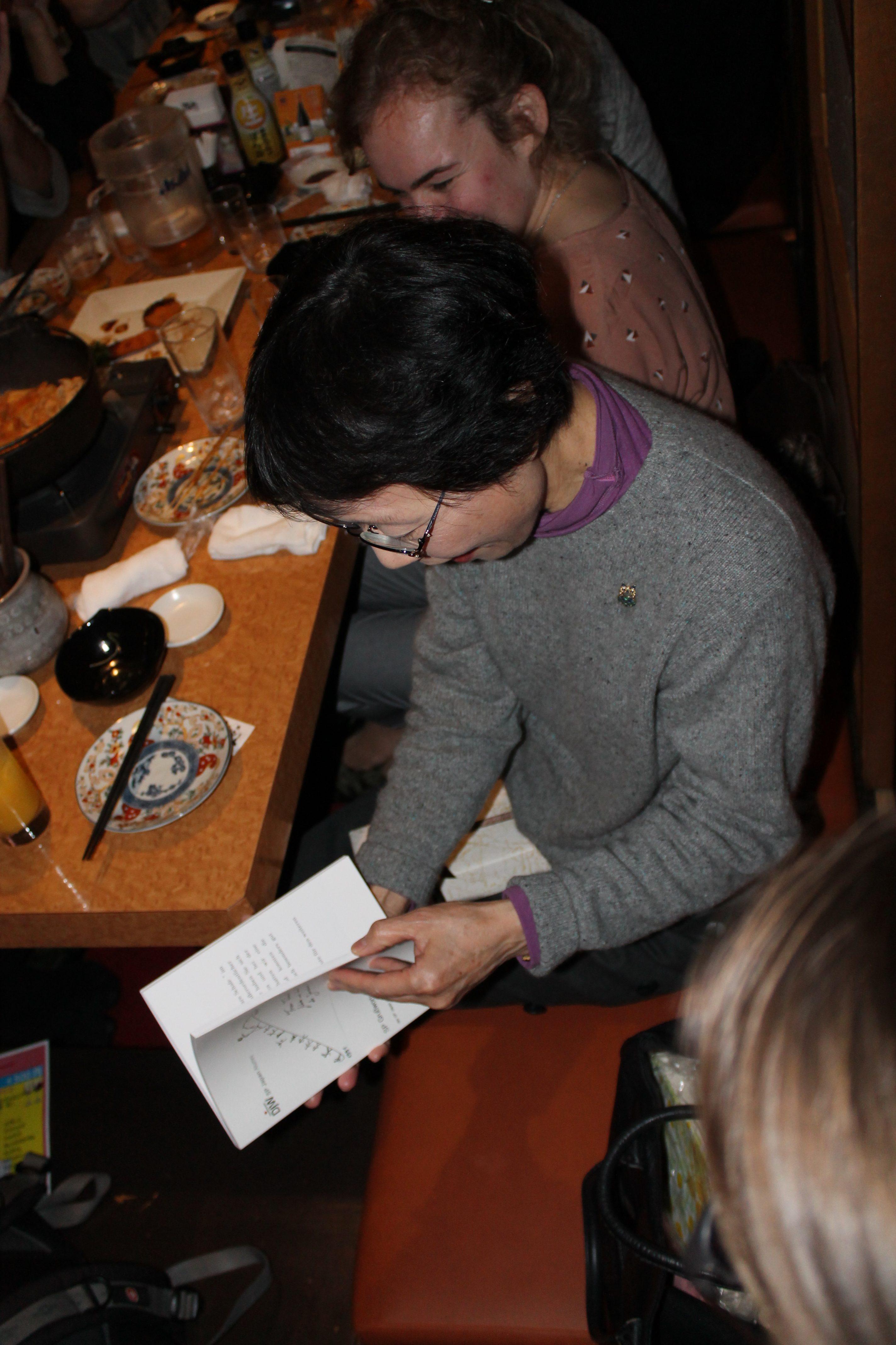 Frau Takeda blaettert durch das Fotobuch